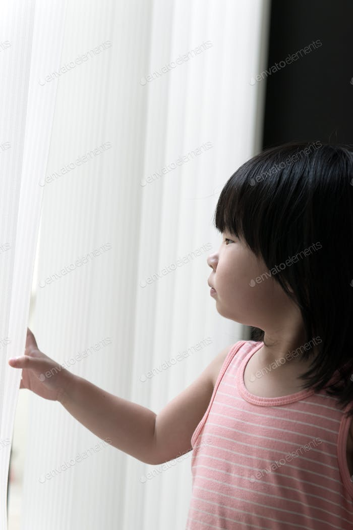 Sad little girl looking at window