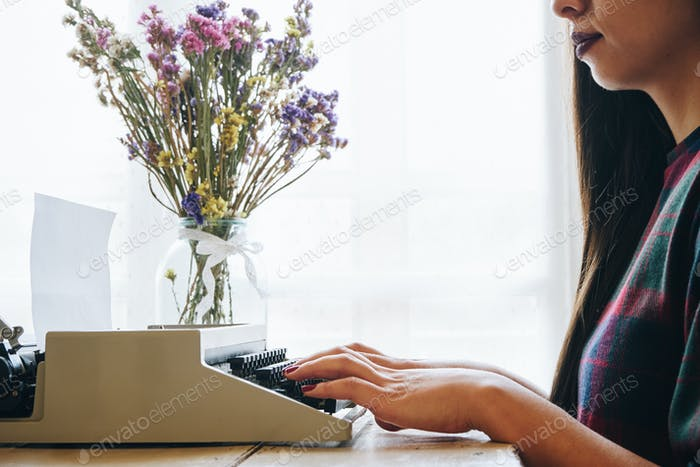 Young woman typing on a vintage typewriter