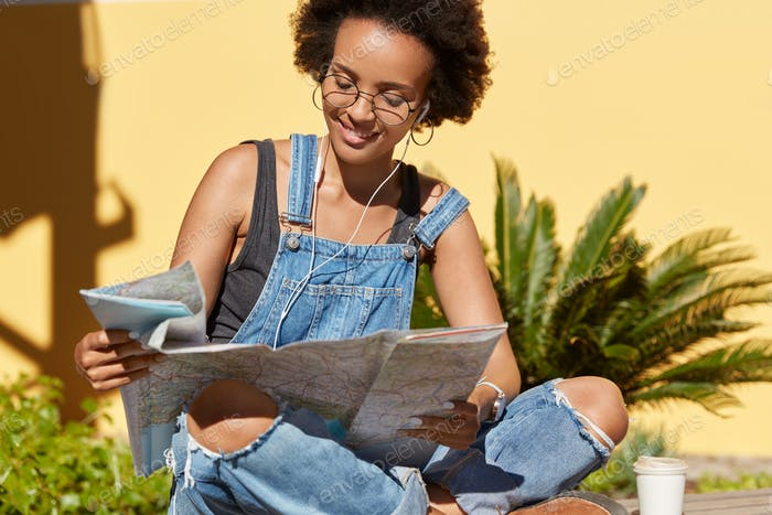 Photo of black lady with crisp hair uses destination map, searches interesting places to visit, like