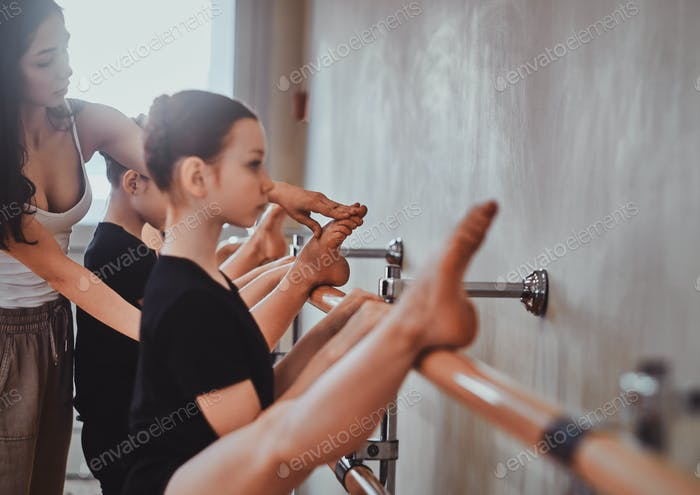 Diligent girls are doing strechening with their talented trainer
