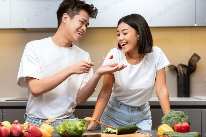 Cheerful Asian Family Couple Cooking Tasting Food Together In Kitchen