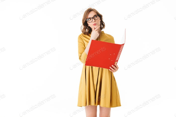 Lady in eyeglasses and yellow dress standing with red folder in hand and thoughtfully looking aside