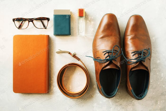 Men's accessories and shoes on gray background. Flat lay of elegant belt, glasses, parfume