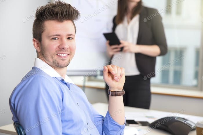 Confident Businessman Smiling While Colleague Holding Tablet Com