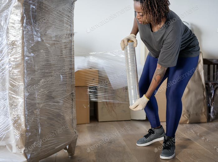Black woman moving furniture