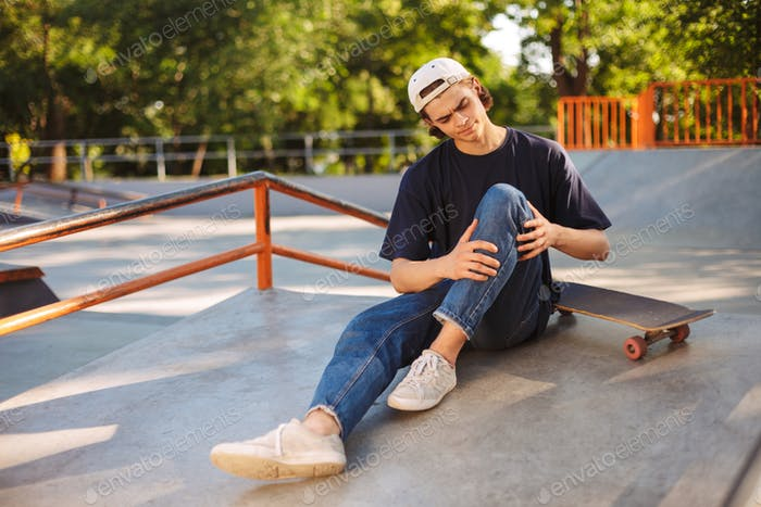 Young upset skater holding his painful leg with skateboard near