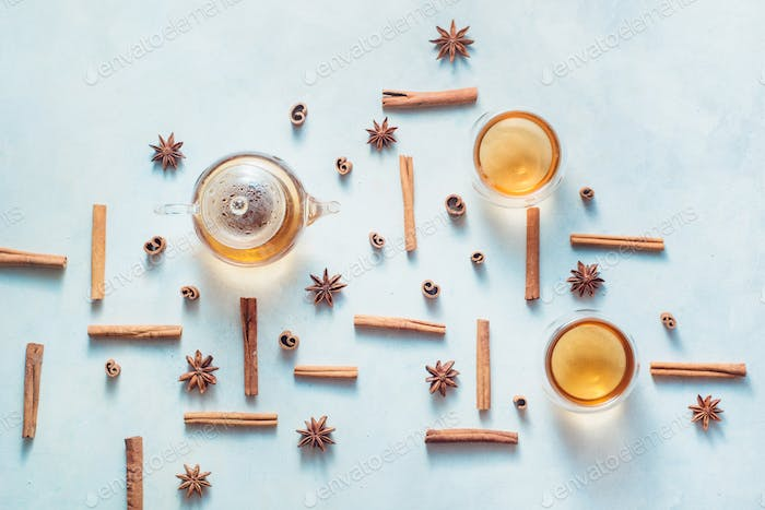 Cinnamon and anise pattern with teapot and tea bowls on a white wooden background with copy space