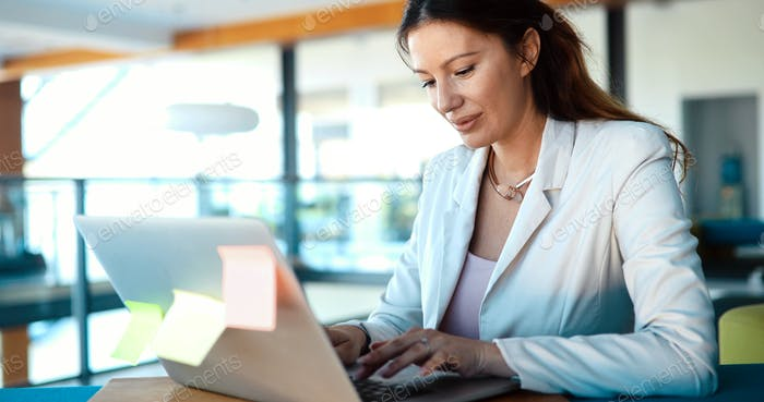 Attractive young female architect working on laptop