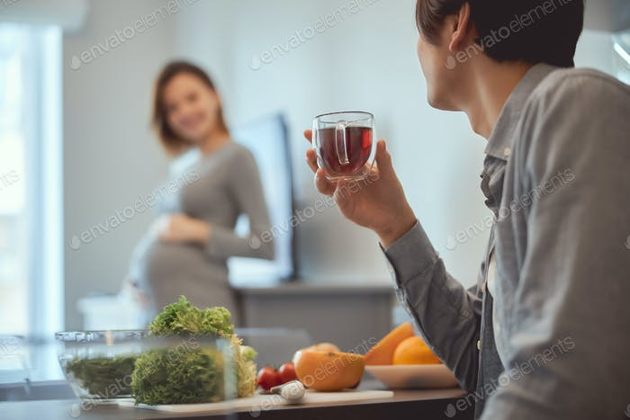 Couple in the kitchen enjoying beauty of pregnancy