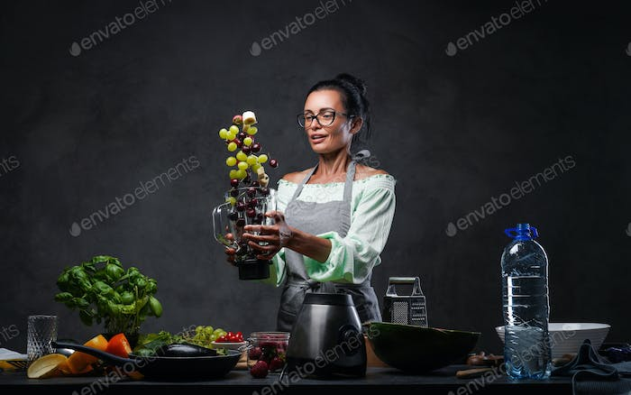 Middle-aged woman in glasses and apron tossing fresh fruit in the air from a blender in kitchen