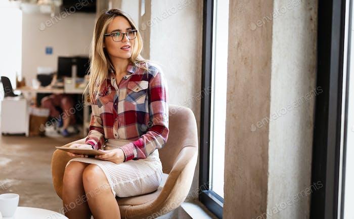 Retrato de una diseñadora sonriente, estudiante, mujer de negocios freelancer usando tablet computer