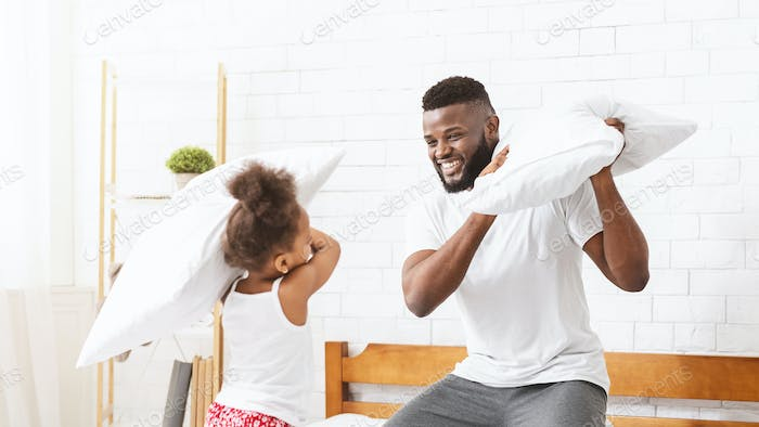 Loving black dad having pillow fight with little playful daughter