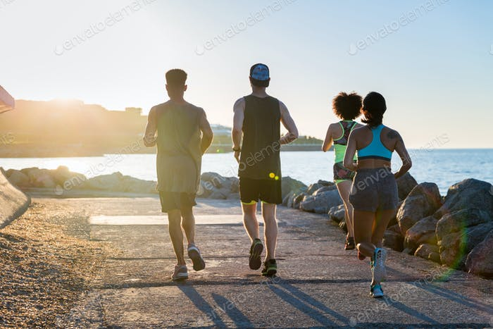Back view of a group of young sporty friends jogging