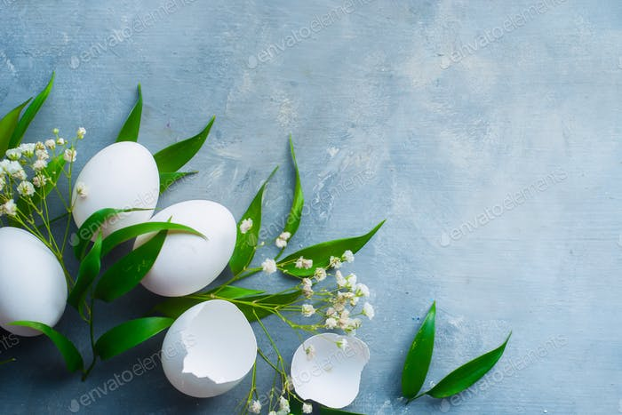 Overhead raw eggs cooking background. Spring leaves and flowers. High key minimalist cooking concept