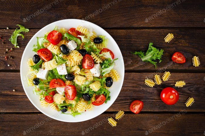Italian pasta salad with fresh tomato, cheese, lettuce and olives