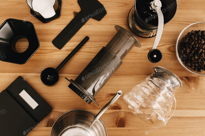 Steel kettle, scales, manual grinder, aeropress, coffee beans top view