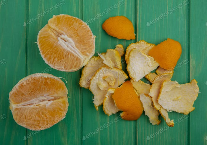 top view peeled orange with peel on green background