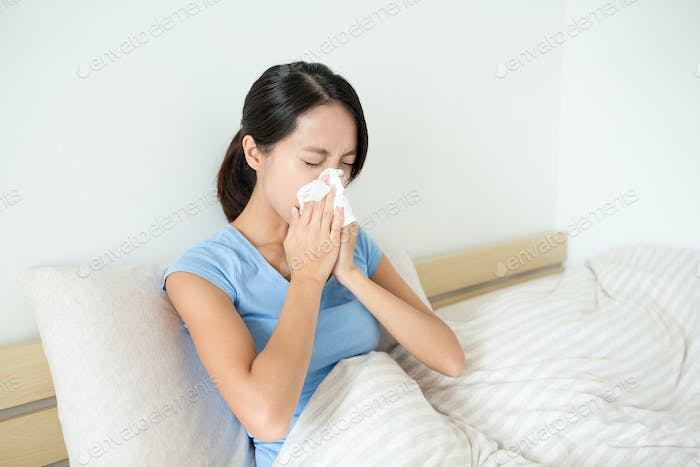 Asian woman sneezing on bed