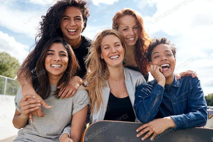 Portrait Of Female Friends With Skateboard In Urban Skate Park