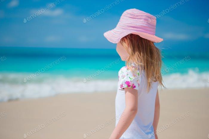 Adorable little girl walking along white sand Caribbean beach
