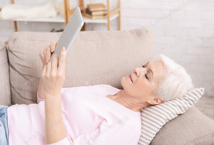 Senior lady web surfing on digital tablet at home