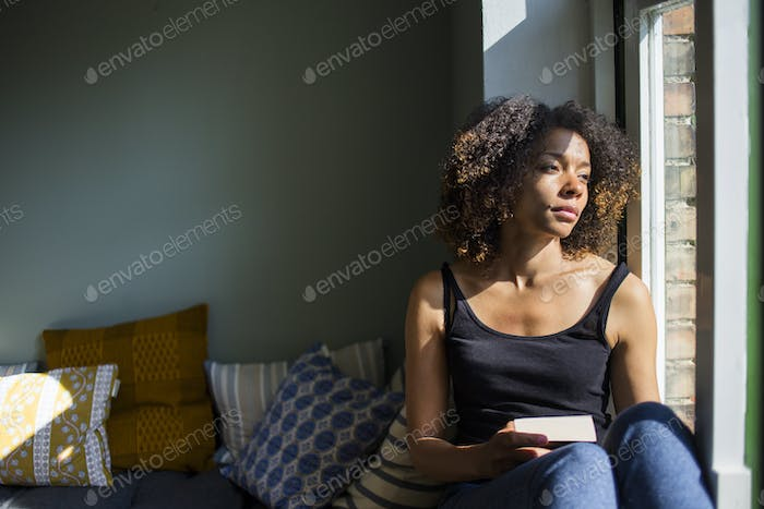 Woman sitting on sill and looking through window