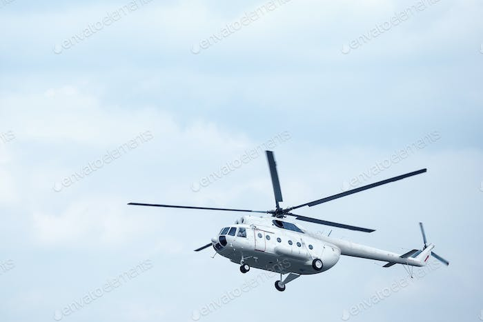 White helicopter in the blue sky