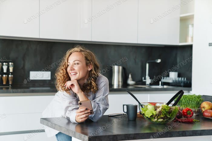 Smiling young woman using smartphone in kitchen
