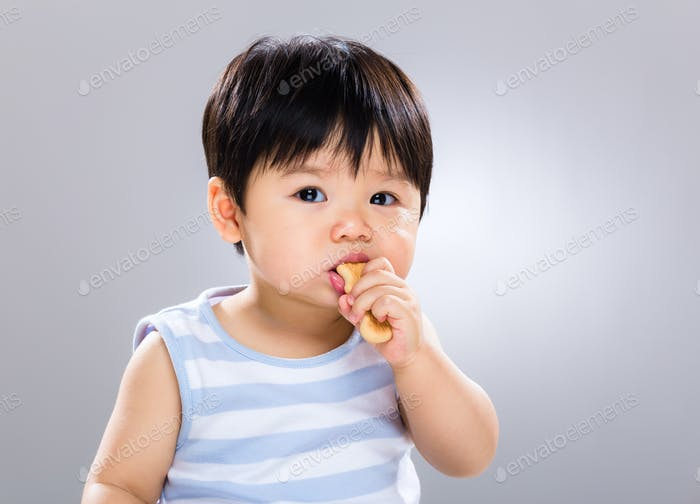 Little boy eat biscuit