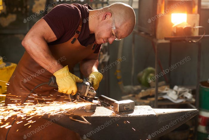 Young workman polishing metal with grinder