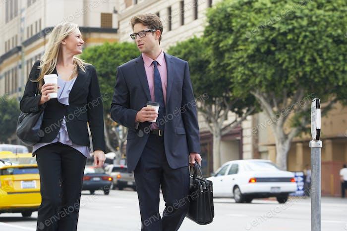 Geschäftsmann und Geschäftsfrau in Straße mit Kaffee zum Mitnehmen