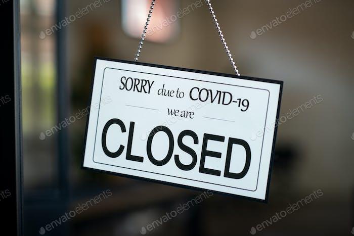 Cartel cerrado colgando en la puerta del café debido a Covid-19