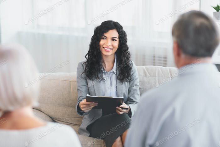 Senior couple talking to financial advisor at her office