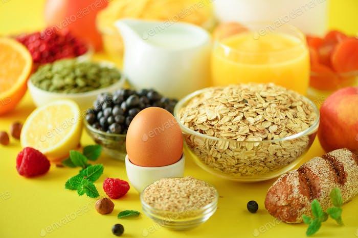 Deliciosos ingredientes para el desayuno. Huevo hervido Suave, copos de avena, nueces, frutas, bayas, leche, yogur