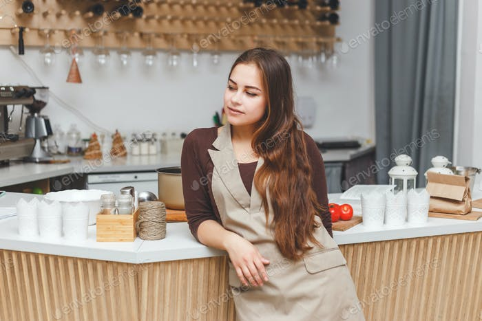 Portrait of beautiful young barmaid wearing apron