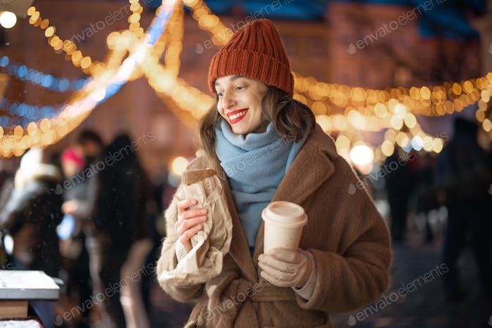 Woman with coffee staying near shopcase in the Christmas market