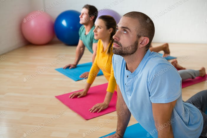 Instructor guiding students in practicing cobra pose at yoga studio