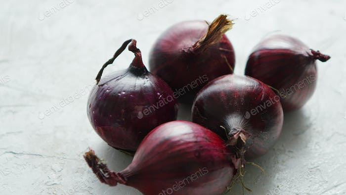 Red onion bulbs on white table