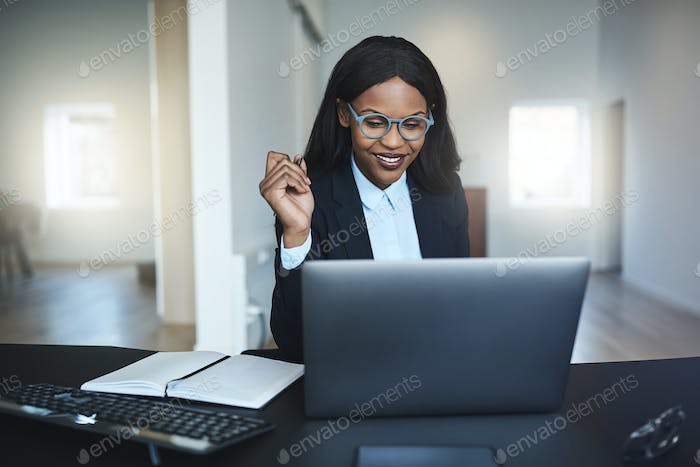 Young African American businesswoman smiling while working on a laptop