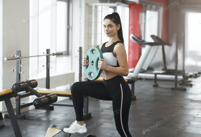 Young woman with barbell weight plate working out in sports club