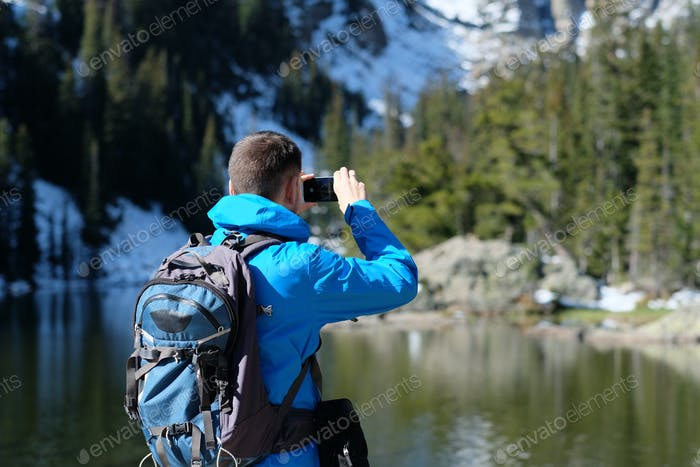 Backpacker taking photo with smartphone