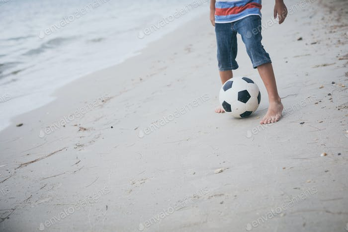 Young little boy playing on the beach with soccer ball.