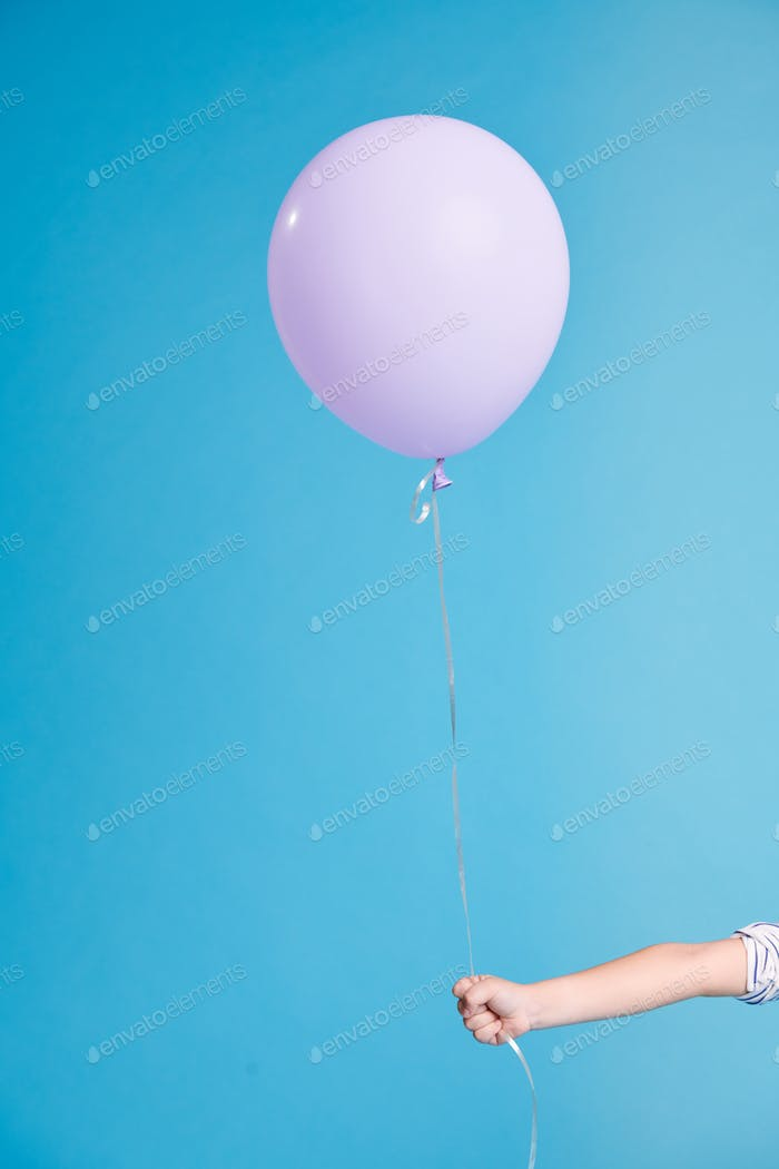 White single birthday balloon in little child hand in isolation