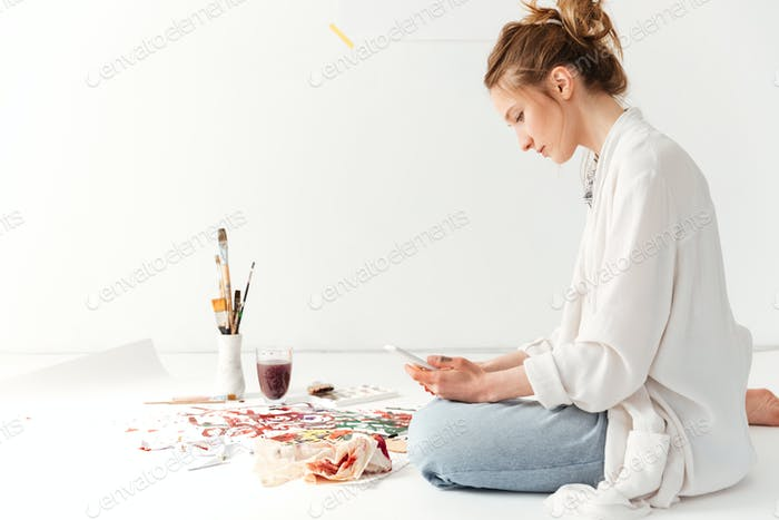 Serious young caucasian lady painter at workspace using phone
