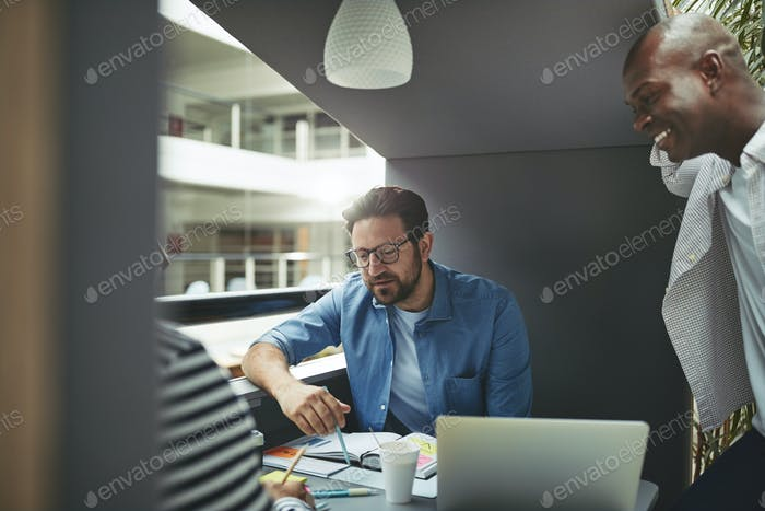 Diverse team of businessmen working in an office meeting pod