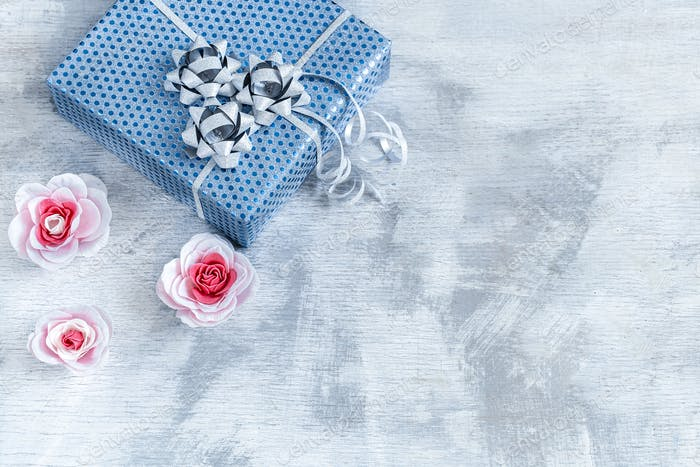Blue gift box on a light wooden background.