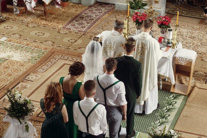 Emotional couple at wedding ceremony in christian catholic church
