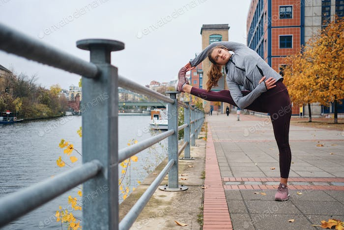 Young attractive sporty woman stretching on empty city street