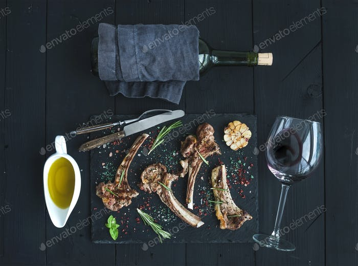 Rack of Lamb with garlic, rosemary, spices on slate tray, wine glass, oil in a saucer and bottle