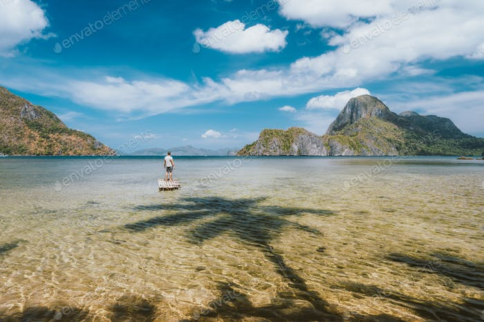 Man staying on bamboo float with impressive view of Cadlao island. Palawan, Philippines. Holiday